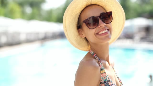 Happy caucasian woman in hat and sunglasses in hands smiles to camera