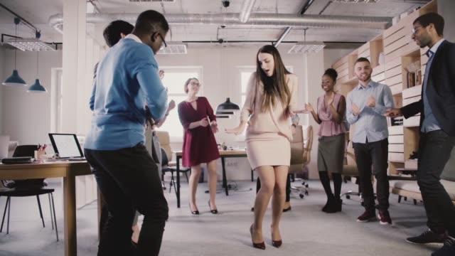 vídeos de stock, filmes e b-roll de empresária de ceo feliz comemorando conquista corporativa com uma dança em velocidade lenta de festa casual escritório multiétnica - festa da empresa