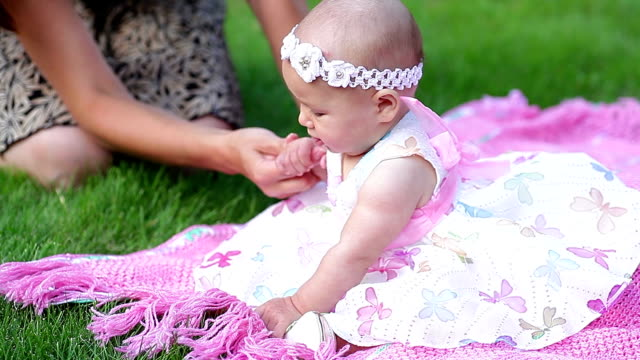 happy cheerful baby girl on pink blanket in park video