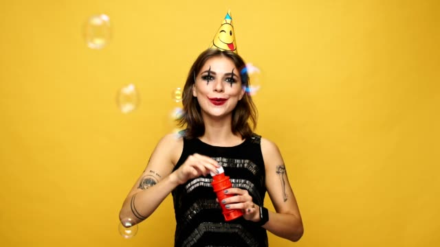 Happy cheerful lady with halloween make up and holiday cap blowing soap bubbles isolated over yellow video