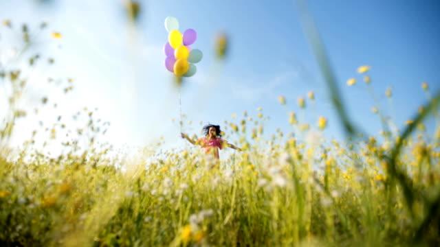 vídeos de stock e filmes b-roll de happy cheerful woman holding balloons and dance - mulher balões