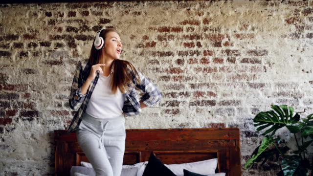 Happy cheerful woman is dancing on bed at home listening to music through wireless headphones. She is wearing casual clothes, nice house interior is visible. video