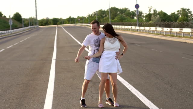 Happy, cheerful young people dancing on an empty road and laugh. Slow motion.