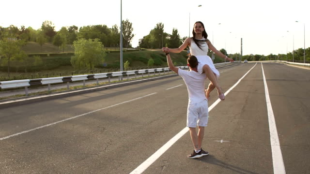 Happy, cheerful young people dancing on an empty road. Slow motion.