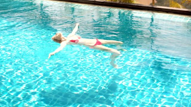 vidéos et rushes de joyeux joyeuse jeune femme dans la suite de natation rouge couché sur l'eau dans la piscine. belle journée ensoleillée - allongé sur le dos