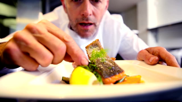 Happy chef garnishing salmon dish video