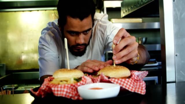 Happy chef placing skewers on burger in kitchen video
