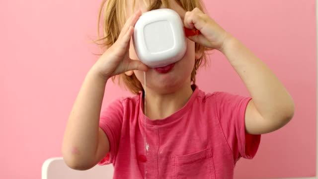 mutlu çocuk içecek süt bir fincan - süt stok videoları ve detay görüntü çekimi