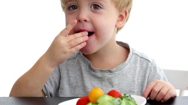 Happy child eating healthy vegetables