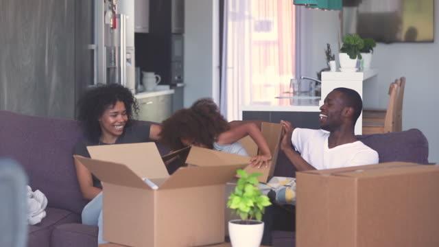 lycklig barn flicka hoppa ur lådan leka med svarta föräldrar - flyttlådor bildbanksvideor och videomaterial från bakom kulisserna