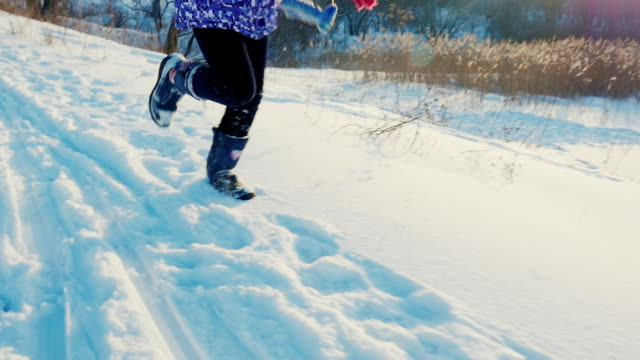 Happy child have fun running on the fresh snow. Laughing happily, positive emotions. Beautiful late afternoon lighting video