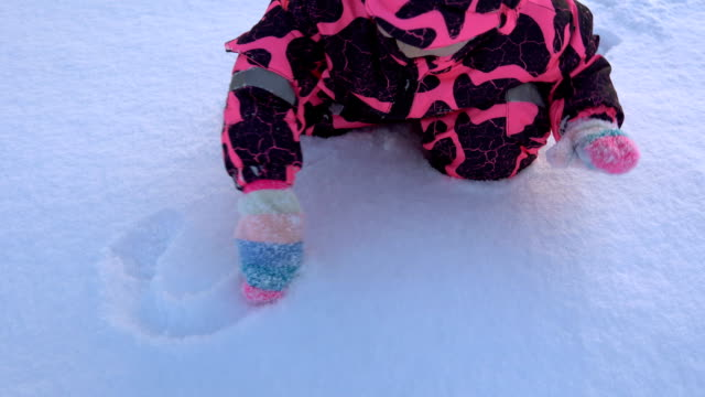 a happy child in a pink overall plays with snow - simbolo concettuale video stock e b–roll