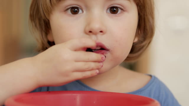 Happy child little boy  eats currant in the summer home kitchen. Closeup.