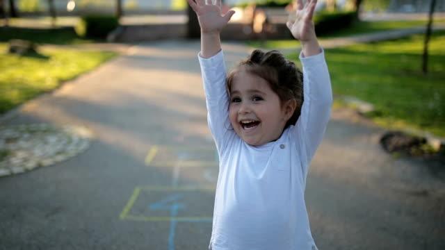 vídeos de stock e filmes b-roll de happy child on a playground playing hopscotch - braços no ar