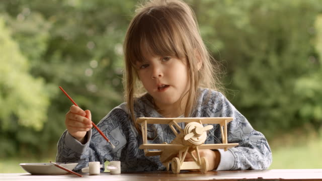 Happy Child Painting a Wooden Airplane Model on a Beautiful Summer Morning at The Porch. video