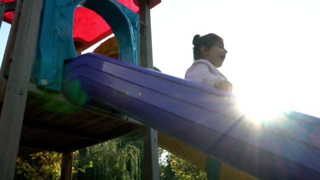 happy child playing on a slide at the playground - scivolo video stock e b–roll