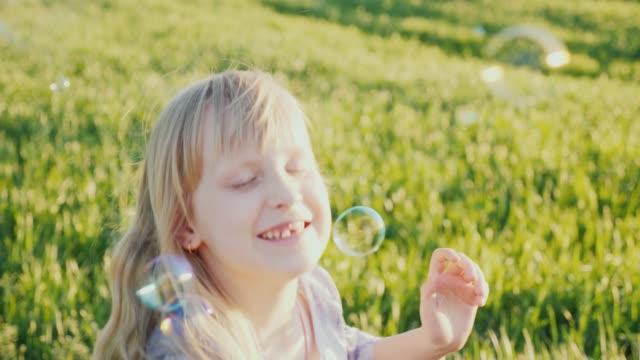 happy child playing with soap bubbles - solo neonati maschi video stock e b–roll