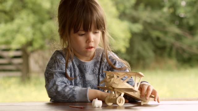 Happy Child Playing With Wooden Airplane Model on a Beautiful Summer Morning at The Porch video