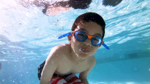 stockvideo's en b-roll-footage met gelukkig kind poseren en onderwater maken van tekens - swimmingpool kids
