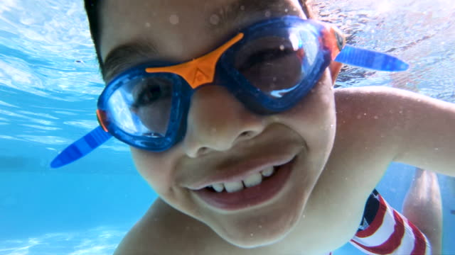Happy Child Posing and Making Signs Underwater High quality stock video of a young 7-year-old boy making hand signs underwater looking into the camera in a bright, clean swimming pool. swimming stock videos & royalty-free footage
