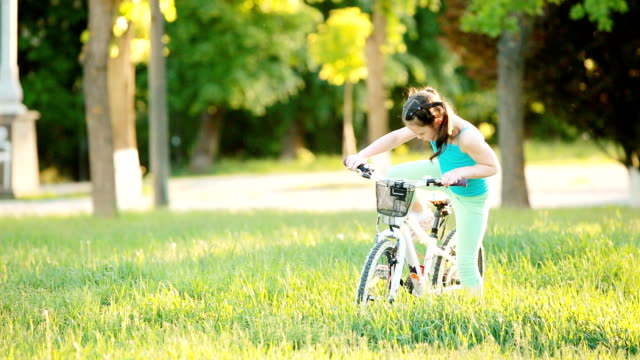 happy child riding a bike in the city park at summer warm day. - cestino della bicicletta video stock e b–roll