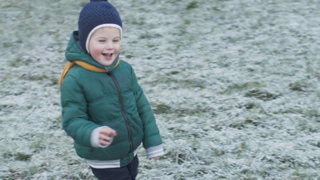 Happy child running on first snow in winter