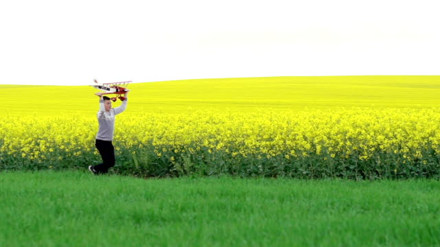 Happy child running with toy airplane near the rape field. Slow motion video