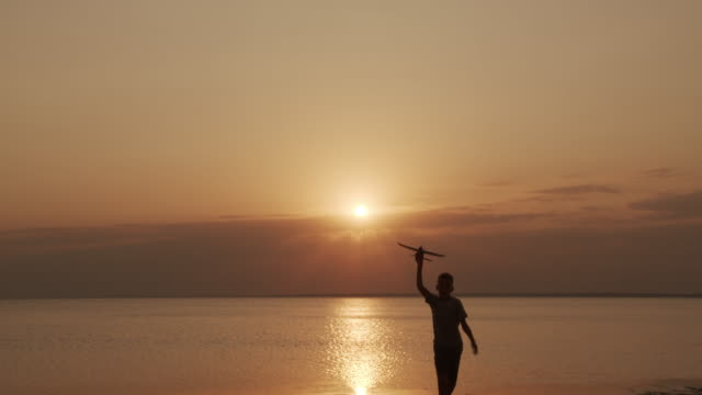 Glückliches Kind läuft mit einem Spielzeugflugzeug auf einem Sonnenuntergang Hintergrund am Meer – Video