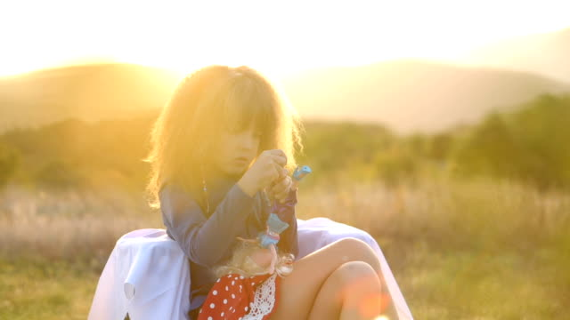 Happy child with doll in sunset