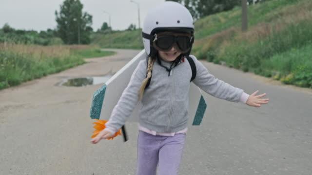 glückliches kind mit spielzeugschaumflügeln und schutzbrille. - raumanzug stock-videos und b-roll-filmmaterial