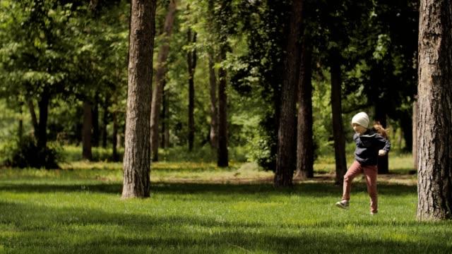 glückliche kindheit, süße mädchen glücklich laufen und springen durch den waldpark - kopfbedeckung stock-videos und b-roll-filmmaterial