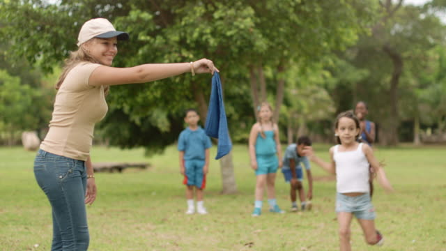glückliche kinder und lehrer spielen im stadtpark - ferienlager stock-videos und b-roll-filmmaterial