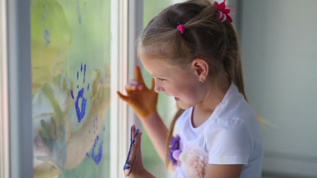 happy children girl draw with palms on the window. painted hands leave a mark on the glass. quarantine. stay home. flash mob society community on self-isolation quarantine pandemic coronavirus. - traccia video stock e b–roll
