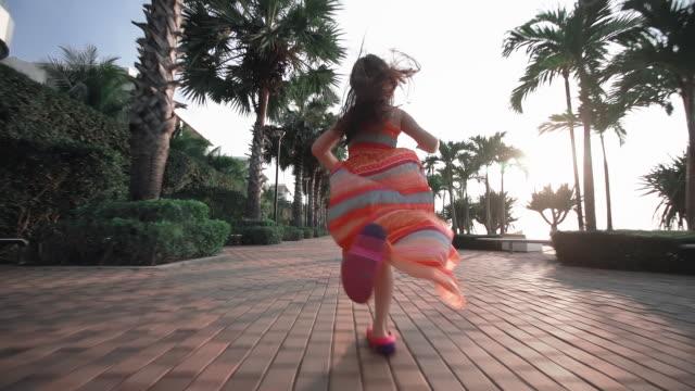 SLO MO Happy children girl running on palm Trees street walk way.