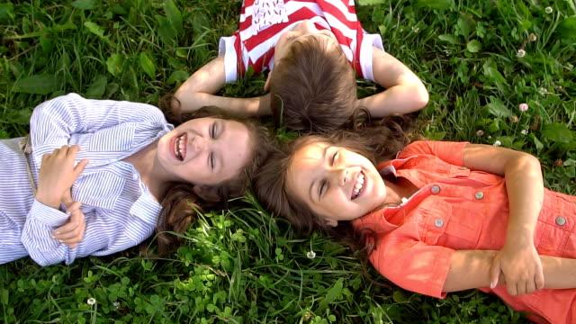 スローモーションで笑い、一緒に草の上に横になっている幸せな子供 ビデオ