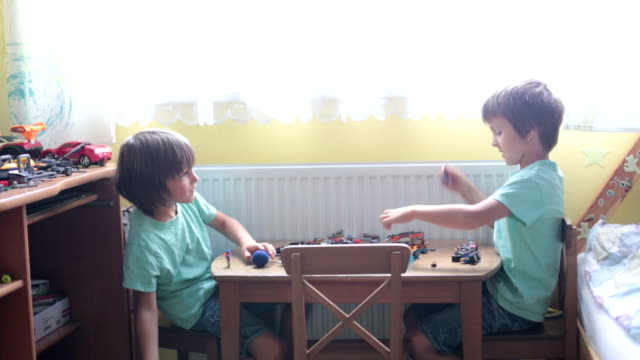 Happy children, playing together at home with construction blocks, indoor video