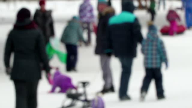 glada barn rida från en kulle i oskärpa. konceptet vinter familj semester, hälsosam livsstil, glada humör. barn tillsammans med fäder och mödrar åka snöskoter och slangar. barn gå med släde, uppblåsta rör och snö-katter. glada barn med - vintersport bildbanksvideor och videomaterial från bakom kulisserna