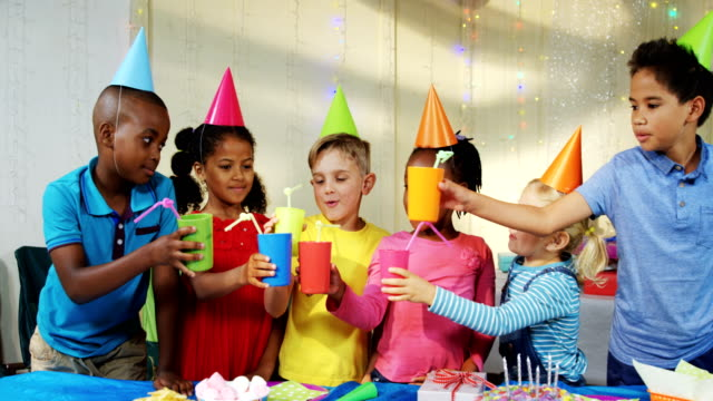 Happy children toasting drinks during birthday party 4k video
