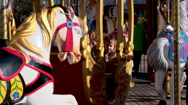 Happy children with father ride carriage on large carousel