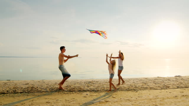 Happy children's games. The elder brother is playing with his sisters, is launching a kite, run together video