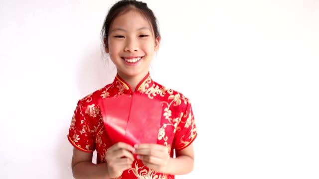 Feliz Año Nuevo chino. Sonriendo Asian girl holding sobre rojo - vídeo