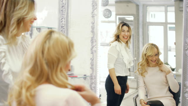 Happy client enjoys her curls in beauty salon video