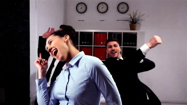 happy colleagues dancing in office room video