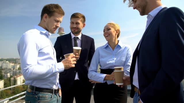 Happy colleagues with coffee cups talking office terrace enjoying work break