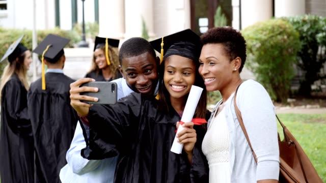 happy college grad takes selfies with parents - celebrazione della laurea video stock e b–roll