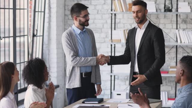 vídeos de stock, filmes e b-roll de feliz aperto de mão gerente da empresa promover elogios trabalhador do sexo masculino no escritório - liquidação evento comercial