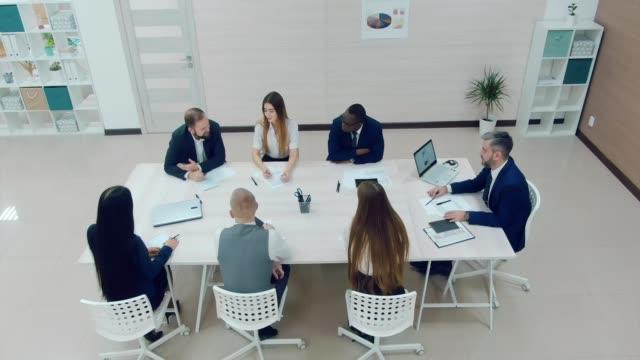 vídeos y material grabado en eventos de stock de compañía feliz de jóvenes empresarios discuten plan financiero. sala de conferencias. vista de cámara desde un helicóptero. - planificación financiera