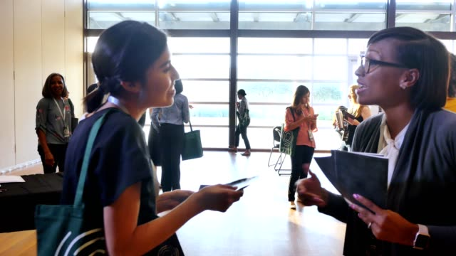 vídeos y material grabado en eventos de stock de feliz saludador de conferencias entrega horario de la conferencia a los asistentes - exhibir