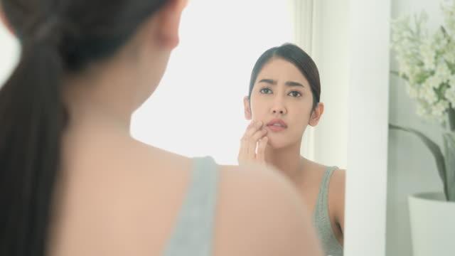 幸せな自信を持って、自宅で午前中に鏡で顔を見て、顔の肌の問題を心配するアジアの美しい若い女性。美容少女は、顔の皮膚の問題を持っています。 - スキンケア点の映像素材/bロール