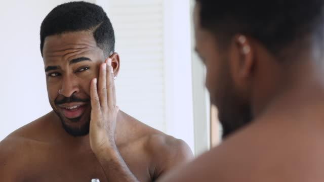 幸せな自信を持って魅力的なアフリカの男はアフタースチャベス香水ローションを適用 - リップクリーム点の映像素材/bロール